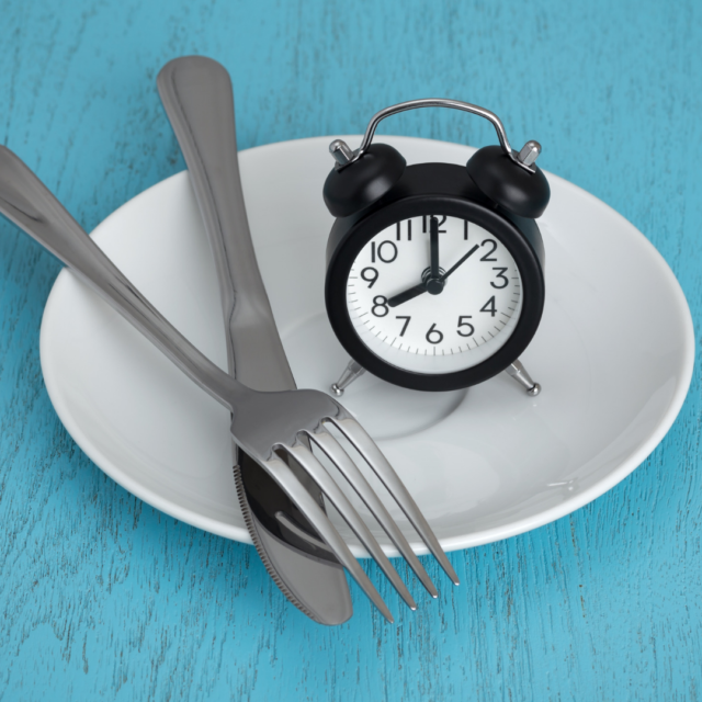 An empty plate with a fork and knife with a clock