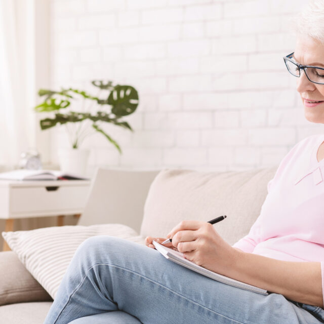 a middle aged woman writing a letter